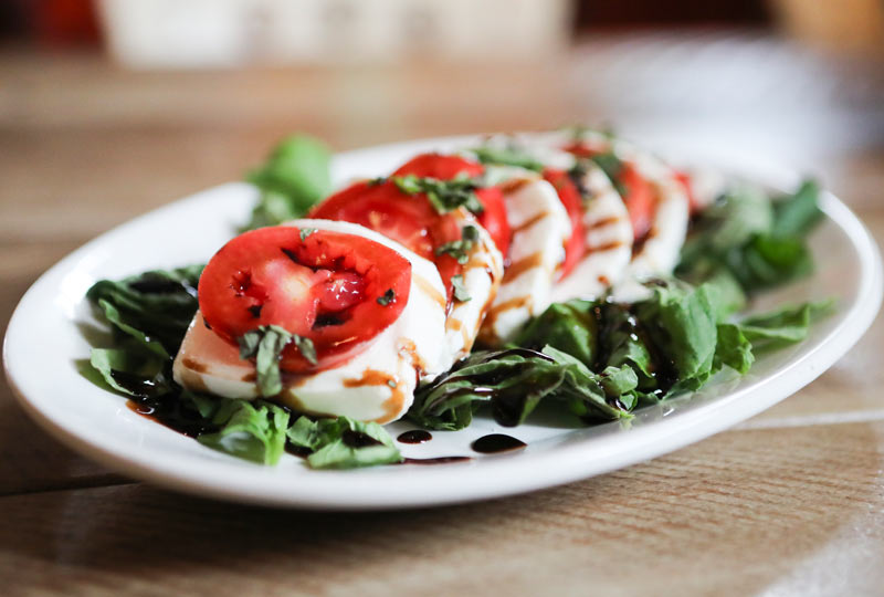 A photo of a Tomato and Mozzarella Salad with Balsamic Vinegar drizzled over top.