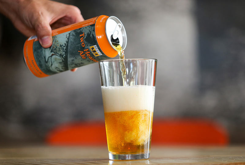 A photo of a man's hand pouring a refreshing looking Bell's Two Hearted Ale beer.
