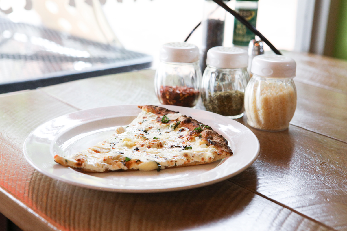 A photo of a piece of white pizza on a plate with red pepper, oregano and Parmesan cheese on the table behind it.